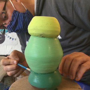 pottery course participant painting his pot made on the potter's wheel