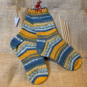 A pair of hand knitted socks with a set of double pointed needles
